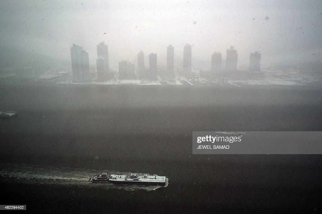 A tugboat sails on the East River during a snow storm in New York on January 26 2015 Thousands of flights were canceled as millions of Americans in...