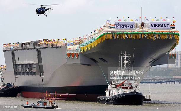 Tugboats guide the indigenouslybuilt aircraft carrier INS Vikrant as it leaves the Cochin Shipyard after the launch ceremony in Kochi on August 12...