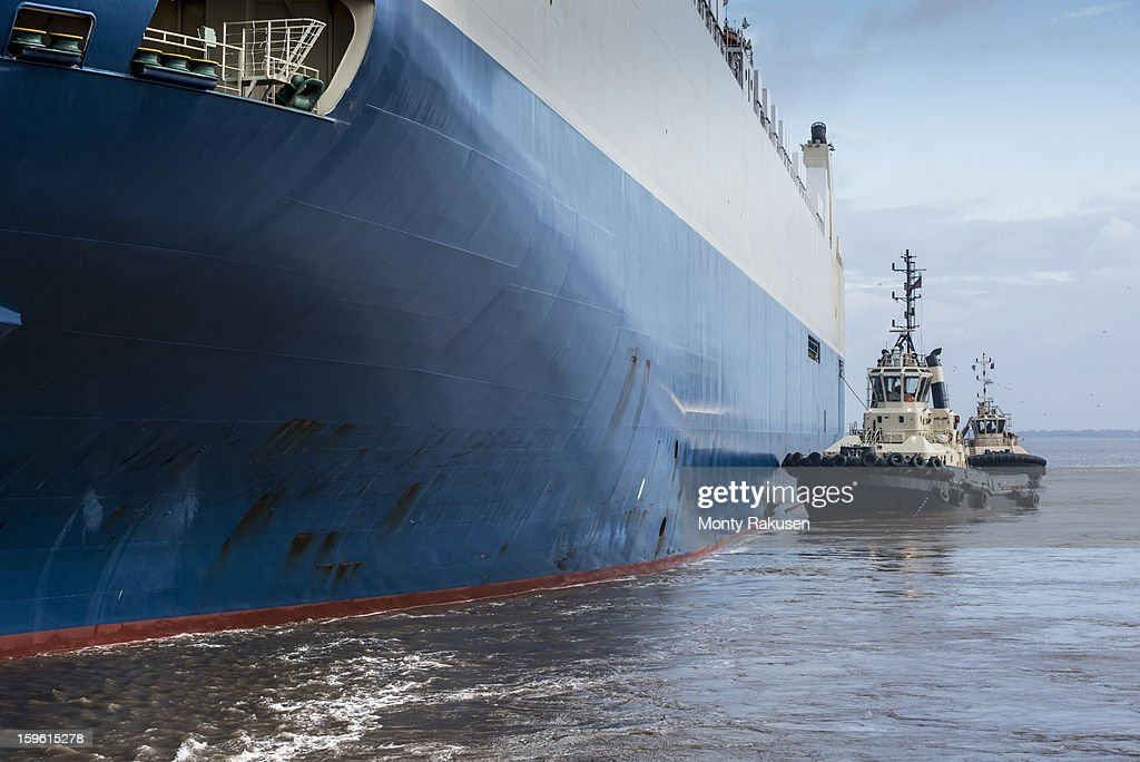 Tugs pushing car ship