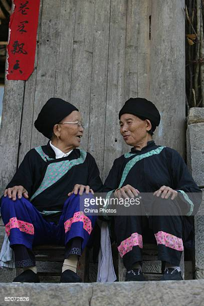 Tujia ethnic senior citizen Tian Dacui talks with a friend during her 80th birthday feast at Keda Village on July 26 2008 in Youyang County of...