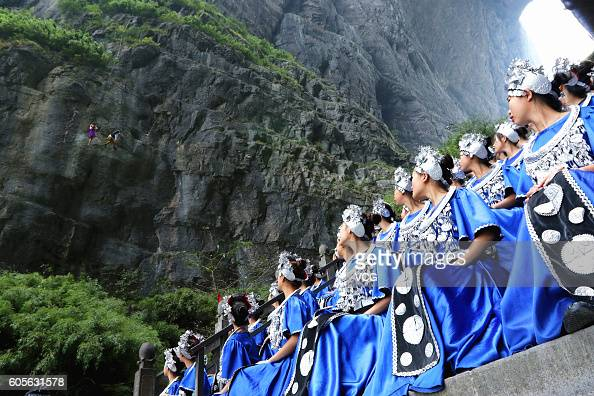 Tujia girls dance on the ground to accompany the Bandaloop dance troupe dancing in the air during a rehearsal at Tianmenshan National Forest Park on...