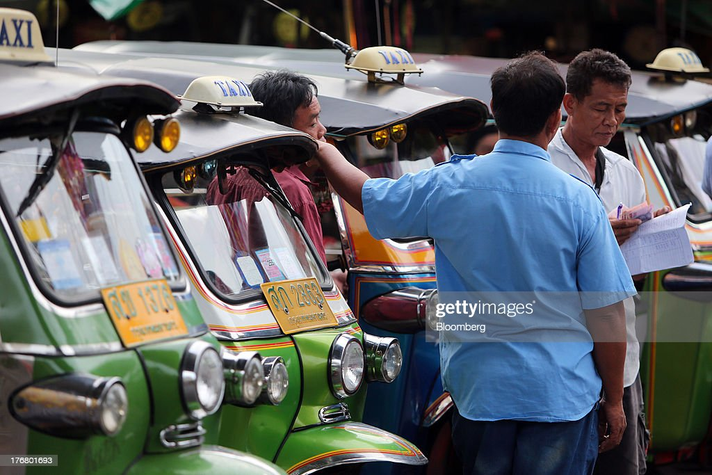 Tuk tuk drivers divide up money outside the Klong Thoei market in Bangkok, Thailand, on Sunday, Aug. 18, 2013. Thai economic growth slowed for a second quarter as exports cooled and local demand weakened, with rising household debt restricting the scope for monetary easing. Photographer: Dario Pignatelli/Bloomberg via Getty Images