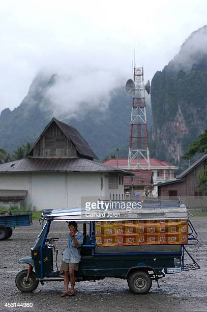 A tuktuk driver at the bus station in Vang Vieng is parked in front of a communications tower which reaches into the clouds The bus station is 160...