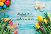 """Tulips, Easter eggs and butterflies on a blue background with """"Happy Easter"""" text"""