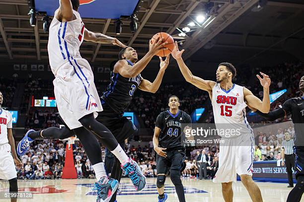 Tulsa Golden Hurricane guard Shaquille Harrison splits the defense of Southern Methodist Mustangs forward Markus Kennedy and center Cannen Cunningham...