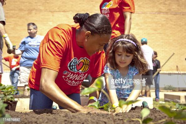 Tulsa Shock player Marion Jones helps Kaytlin Knaebel plant a strawberry plant at Wright Elementary school on May 21 2011 in Tulsa Oklahoma during a...