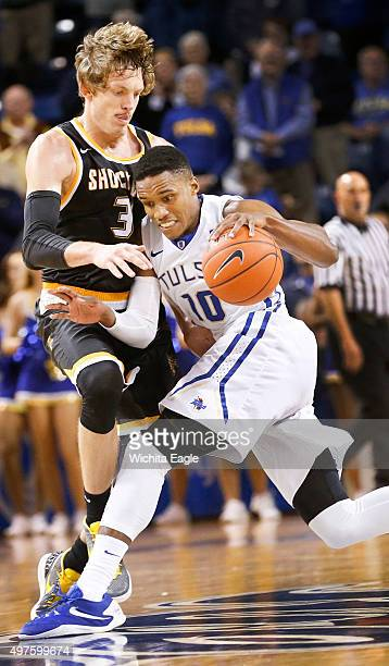 Tulsa's James Woodard runs down the clock as he's guarded by Wichita State's Ron Baker in the fourth quarter at the Reynolds Center in Tulsa Okla on...