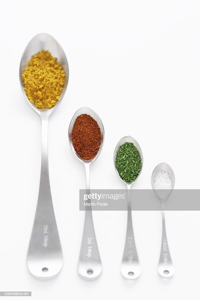 Tumeric, chillie powder, parsley and salt on spoons, close-up