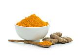 Bowl of turmeric powder with fresh turmeric root