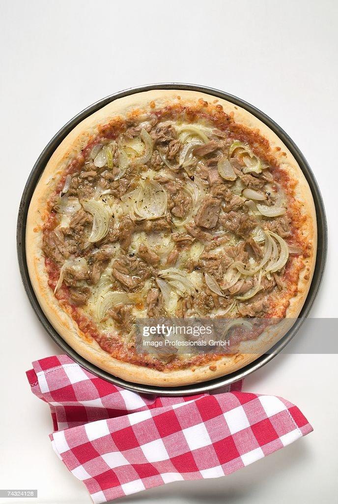 Tuna and onion pizza, checked napkin beside it : Stock Photo