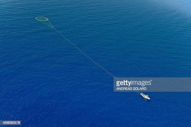 Tuna fishing boat drags a cage of nets on the Mediterranean sea during an environmental group Greenpeace protest action dubbed 'Stop the bluefin tuna...