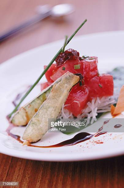 Tuna, spring roll and chive on plate, close-up