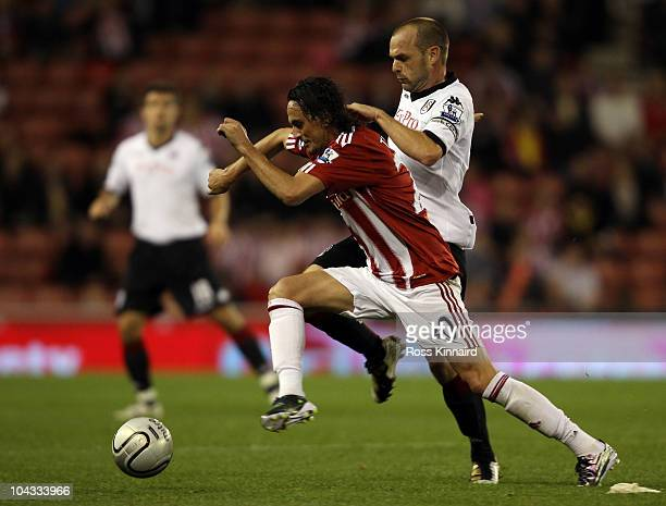 Tuncay of Stoke is challenged by Danny Murphy of Fulam during the Carling Cup 3rd Round tie between Stoke City and Fulham at the Britannia Stadium on...