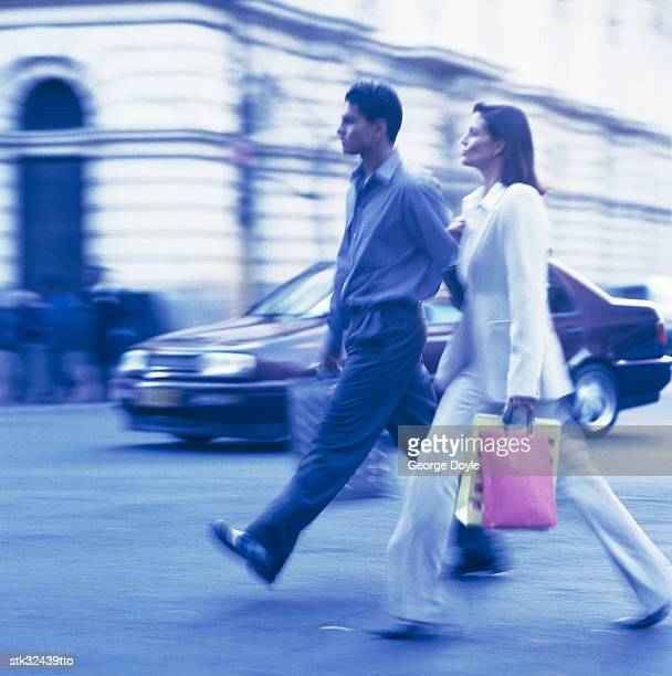 tungsten side profile of a couple walking on a street with shopping bags