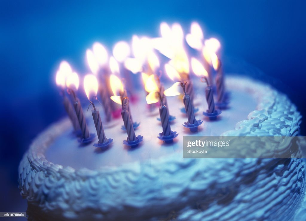 tungsten toned close-up of an array of candles on a birthday cake : Stock Photo