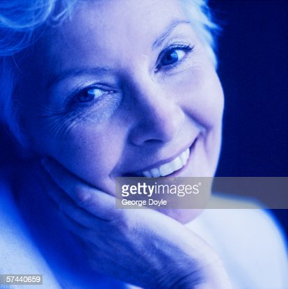 tungsten toned portrait of an elderly woman smiling and holding the side of her face stock foto. Black Bedroom Furniture Sets. Home Design Ideas