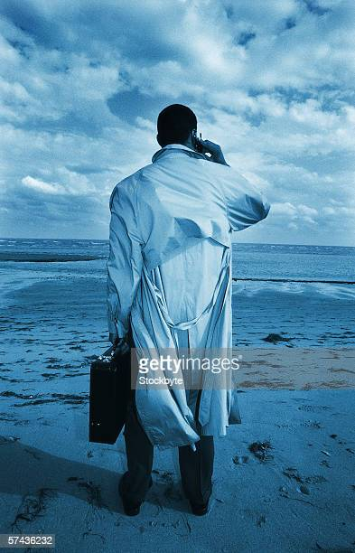 tungsten view from behind of a businessman talking on a mobile phone on the beach