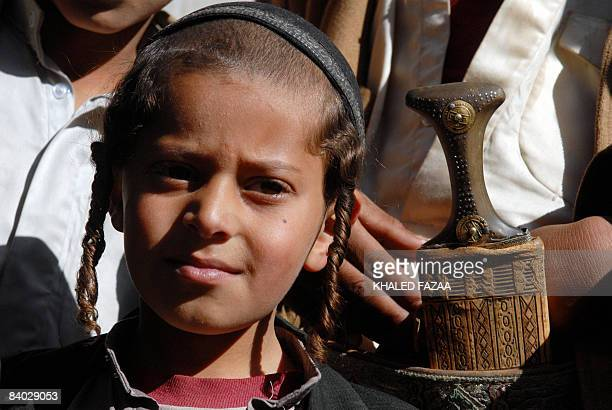 Tuni a Yemeni Jewish boy whose father was killed three days ago stands outside his home with other Yemenis in the village of Raydah in Amran province...