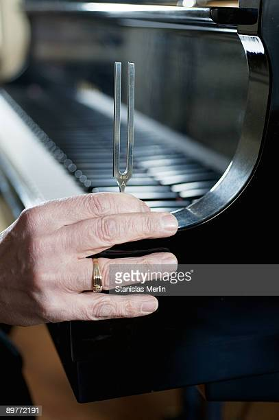 Tuning fork held on grand piano