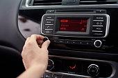 Closeup shot of a driver tuning  a car radio