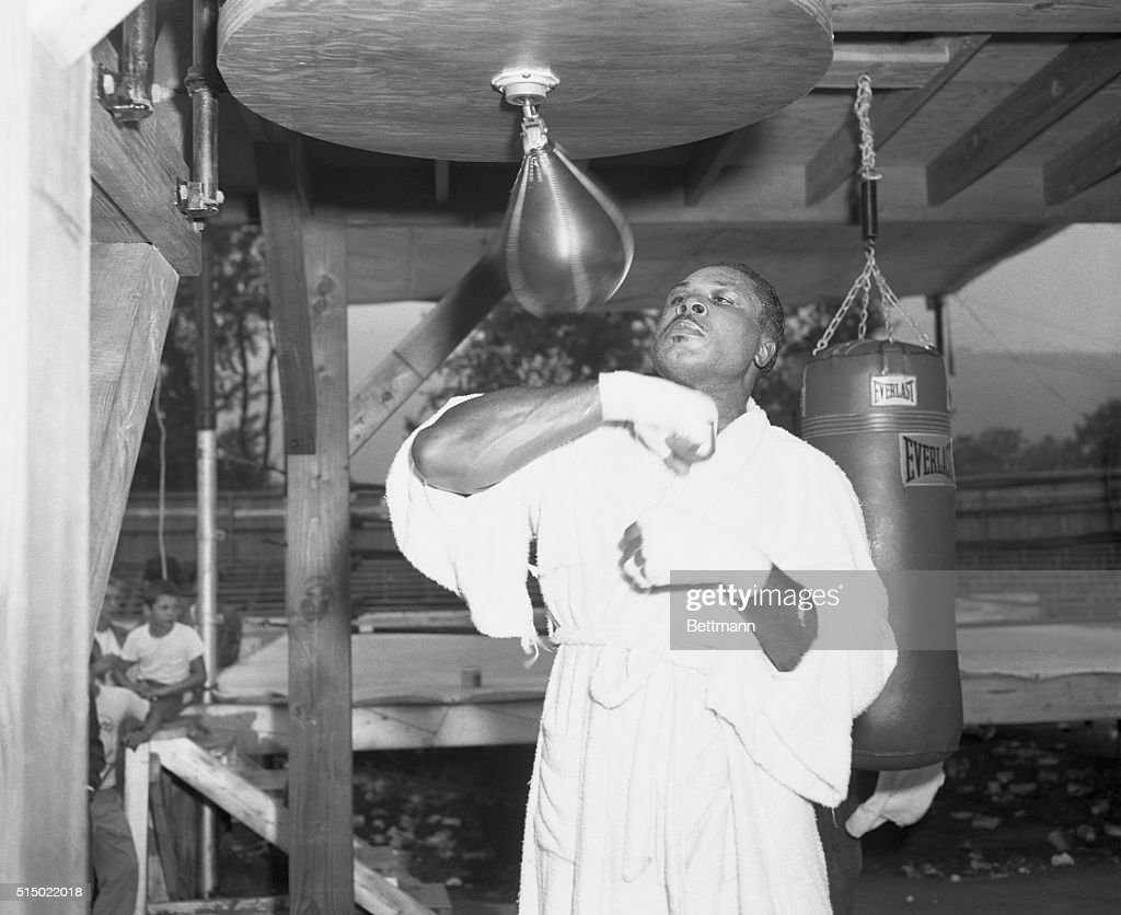 Tuning Up for the Big Fight. North Adams, Massachusetts: Light heavyweight champ <a gi-track='captionPersonalityLinkClicked' href=/galleries/search?phrase=Archie+Moore&family=editorial&specificpeople=93092 ng-click='$event.stopPropagation()'>Archie Moore</a>, who says he's going to knock the heavyweight crown off the head of Rocky Marciano, is shown working out with a punching bag at his North Adams, Massachusetts training camp. Moore will meet Marciano for the World Heavyweight Title in Yankee Stadium on September 20th.