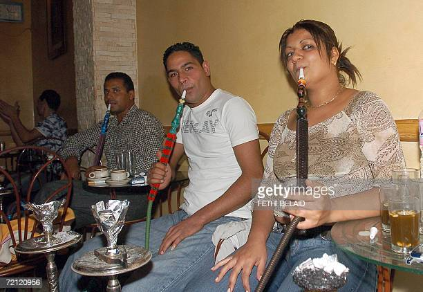 A Tunisian woman smokes a 'chicha' after Iftar in the medina bar in Tunis 08 October 2006 night during the Muslim Holy month of Ramadan During...
