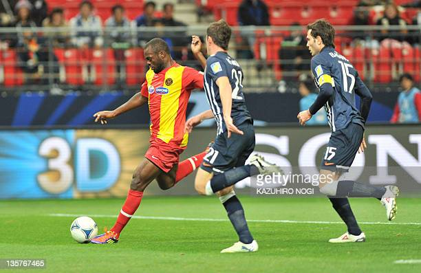 Tunisia club Esperance player Yannick Ndjeng shoots the ball past Hiram Mier and Jose Maria Basanta of Mexican side Monterrey during their football...