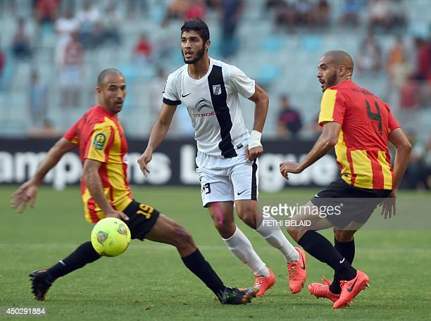 Tunisia CS Sfax forward Ferjani Sassi passes the ball through Esperance of Tunis players Houcine Ragued and Khaled Mouelhi during their CAF Champions...
