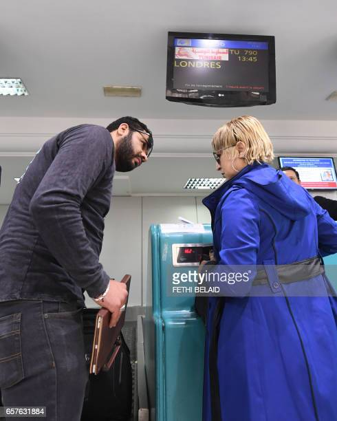 A Tunisian Airlines employee instructs Tunisian couple bound for London to pack away their electronics in their luggage as they checkin for a flight...