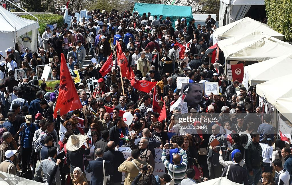 Tunisian and international activists shout slogans and wave flags during the World Social Forum in Tunis on March 25 2015 The WSF is an annual...