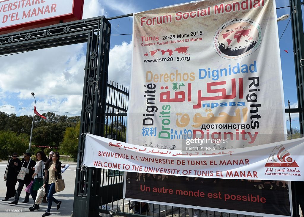 Tunisian and international activists walk next to a banner advertising the World Social Forum in Tunis on March 25 2015 The WSF is an annual meeting...