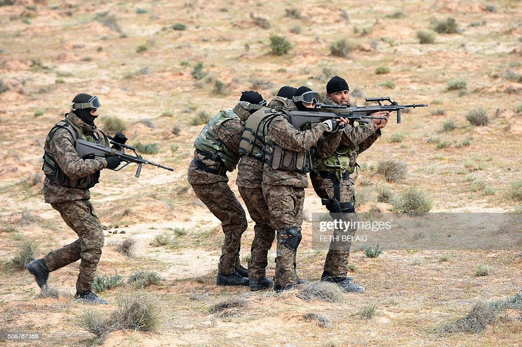 Tunisian army special forces take part in a military exercise near a trench dug along the Libyan border on February 6, 2016, near the Ras Jedir crossing point. The construction of a barrier, which includes berms and trenches, along the Libyan border from Ras Jedir on the Mediterranean coast to Dhiba was announced in 2015 after a terrorist attack on the national museum in Tunis killed 22 people. / AFP / FETHI BELAID