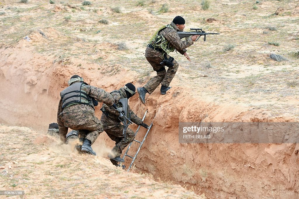 Tunisian army special forces take part in a military exercise on a trench dug along the Libyan border on February 6, 2016, near the Ras Jedir crossing point. The construction of a barrier, which includes berms and trenches, along the Libyan border from Ras Jedir on the Mediterranean coast to Dhiba was announced in 2015 after a terrorist attack on the national museum in Tunis killed 22 people. / AFP / FETHI BELAID