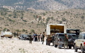 Tunisian army stand guard near a demolished vehicle following a roadside bomb in the mountainous border region near Algeria where security forces...