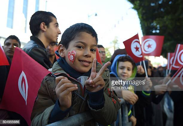 A Tunisian boy flahse the Vsign and holds his national flag during a rally on Habib Bourguiba Avenue in Tunis on January 14 to mark the fifth...