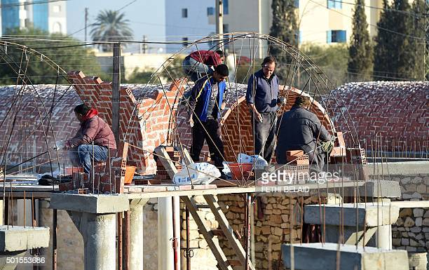 Tunisian builders work at the construction site of a new marketplace on December 15 in the impoverished central town of Sidi Bouzid three days ahead...