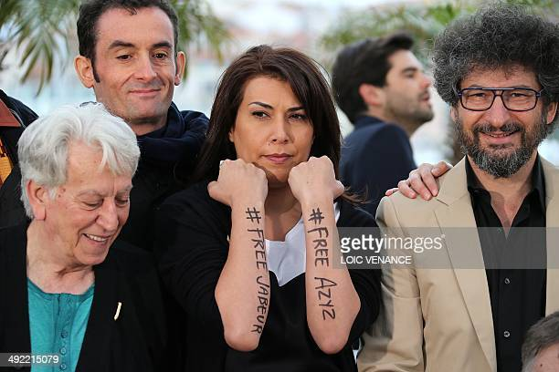 Tunisian cartoonist Willis from Tunis shows her forearms reading '#Free Azyz #Free Jabeur' in support of the release of Tunisian bloggers Jabeur...