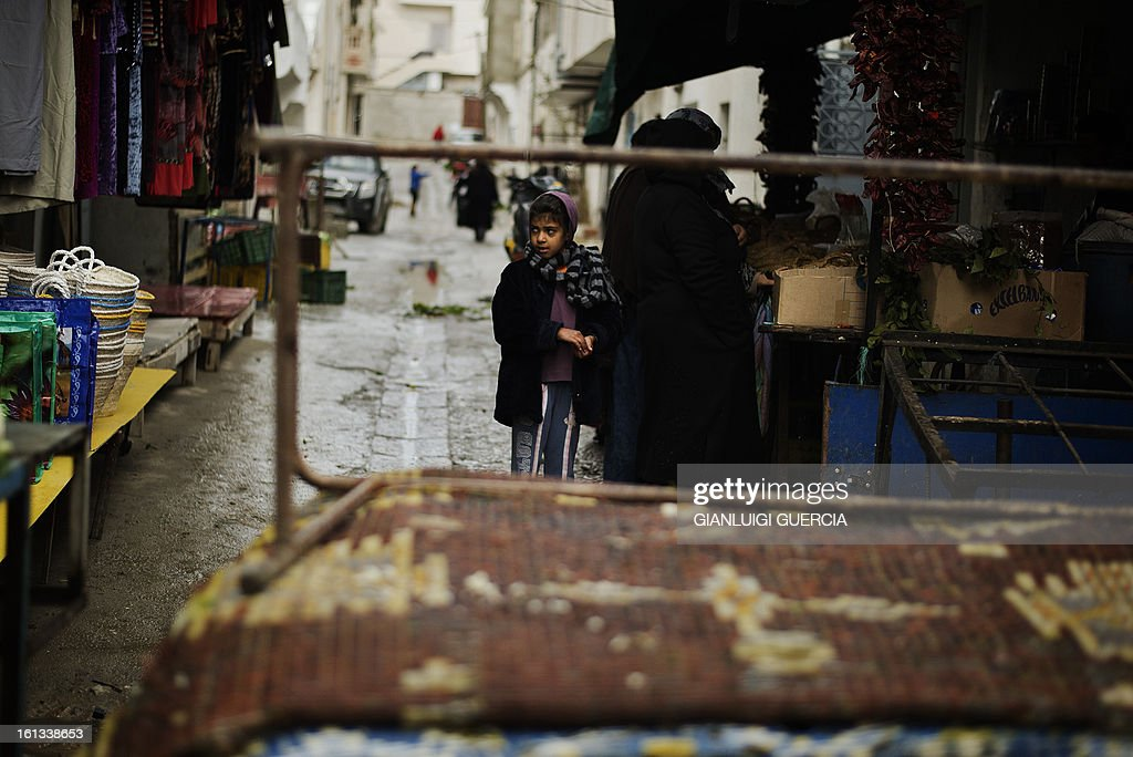 A Tunisian child looks on as a woman shops from a street vendor at a local market in the Kabaria neighbourhood on the outskirts of Tunis on February 10, 2013. After clashes with demonstrators that the interior ministry said left one policemen dead and 59 colleagues wounded, security forces remain on a state of alert with the army deployed nationwide. AFP PHOTO/GIANLUIGI GUERCIA