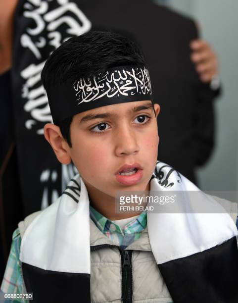 A Tunisian child wearing a bandana that reads in Arabic ''There is no god but Allah and Mohammed is his prophet' attends a speech at the radical...