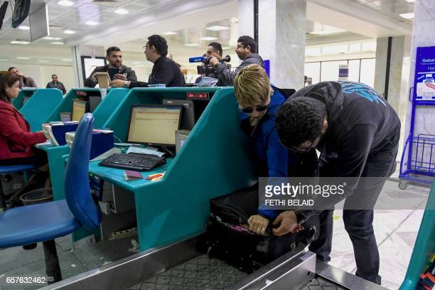 A Tunisian couple bound for London pack away their electronics in their luggage as they checkin for a flight at TunisCarthage International Airport...