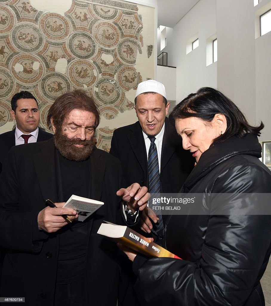 Tunisian Culture Minister Latifa Lakhdhar (R) asks for the signature of French-Jewish writer <a gi-track='captionPersonalityLinkClicked' href=/galleries/search?phrase=Marek+Halter&family=editorial&specificpeople=768328 ng-click='$event.stopPropagation()'>Marek Halter</a> (2nd-L) next to French Imam Hassen Chalghoumi (2nd-R) at the Bardo Museum in Tunis on March 26, 2015, in solidarity with victims of the Tunis' museum attack. Tunisia said that it had arrested 23 suspects in connection with last week's jihadist massacre at the country's national museum.