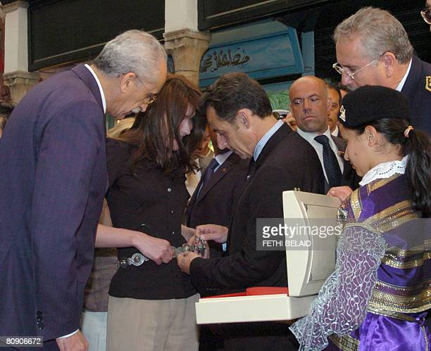 Tunisian culture minister Mohamed Abdeaziz Achouri watches as French President Nicolas Sarkozy places a silver girdle arround his wife Carla...