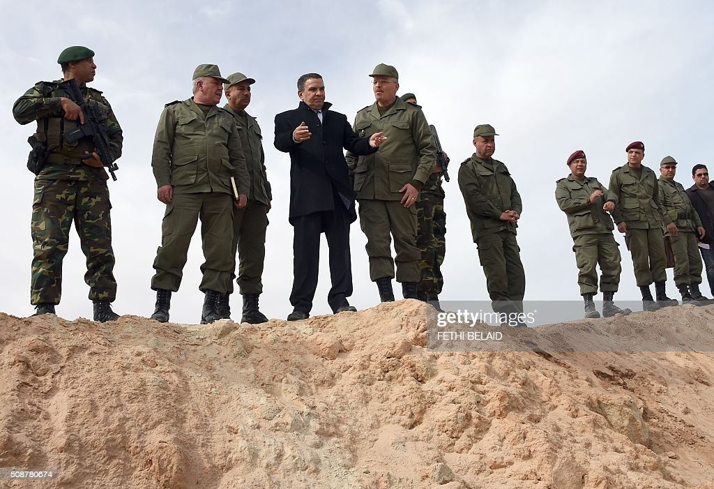 Tunisian Defense Minister Farhat Horchani (C)attends the presentation of a ditch and takes part in a military exercise near a trench dug along the Libyan border on February 6, 2016, near the Ras Jedir crossing point. The construction of a barrier, which includes berms and trenches, along the Libyan border from Ras Jedir on the Mediterranean coast to Dhiba was announced in 2015 after a terrorist attack on the national museum in Tunis killed 22 people. / AFP / FETHI BELAID
