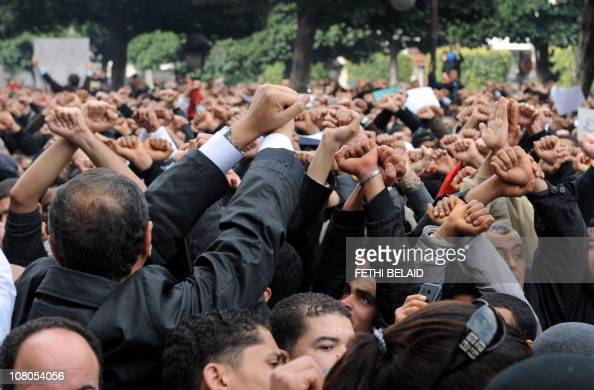 Tunisian demonstrators hold up their hands as if they are handcuffed on January 14 2011 and shout slogans demanding the departure of President Zine...