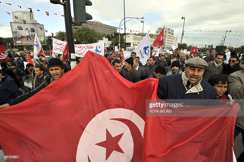 Tunisian Ennahda party supporters holds up the national flag as they take part in a rally to show support for the ruling Islamist party, in which the Ennahda-dominated coalition holds a majority, on February 9, 2013, in the capital Tunis, three days after the assassination of Chokri Belaid, an outspoken critic of the Islamists. Thousands of people protested in central Tunis shouting pro-Islamist and anti-French slogans, a day after the funeral Belaid which became a mass rally against the ruling party.