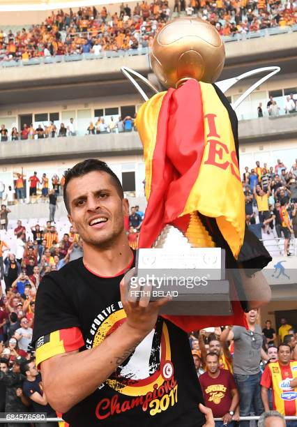 Tunisian Esperance team captain Khalil Chamam holds the trophy after wining the Tunisian Championship match against Tunisia's Etoile du Sahel at the...