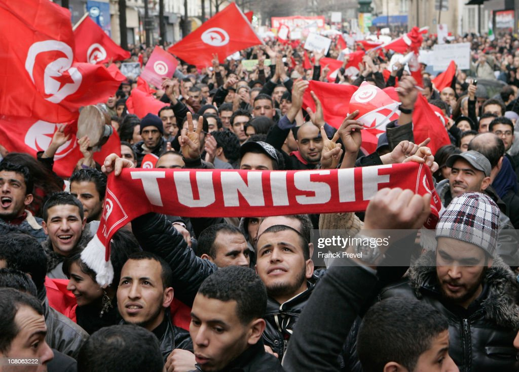 Tunisian expatriates shout slogans while holding Tunisian flags as they demonstrate on January 15 2011 in Paris France Zine alAbidine Ben Ali...