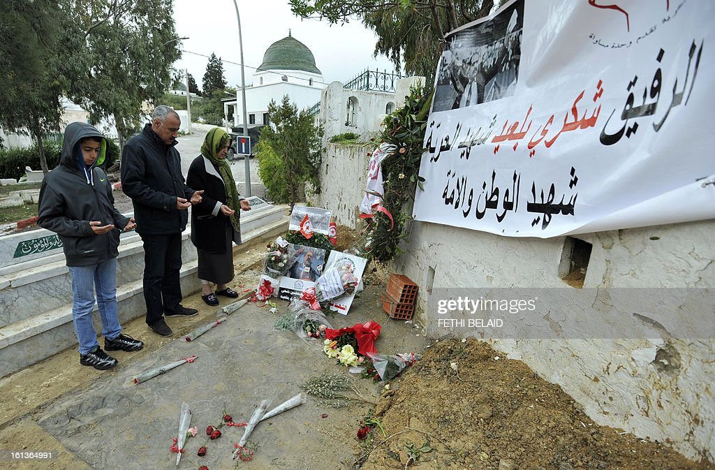 A Tunisian family pray at the grave side of assassinated opposition leader Chokri Belaid in the el-Jellaz cemetery, on February 10, 2013, in the capital Tunis. Tunisian Prime Minister Hamadi Jebali's gamble on forming a new government in defiance of his own Islamist party after the assassination of Belaid has left Tunisia in political limbo. AFP PHOTO / FETHI BELAID