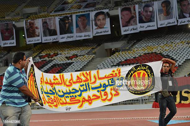 Tunisian fans hold a banner reading in Arabic 'AlAhly martyrs are in the hearts of Esperance de Tunis' in front of portraits of the victims who died...