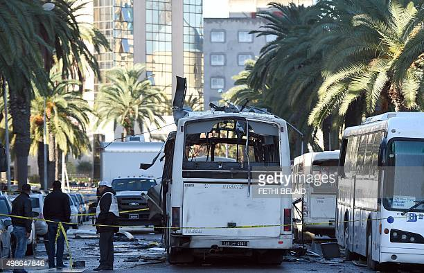Tunisian forensic police inspect the wreckage of a bus in the aftermath of a bomb attack on a bus transporting Tunisia's presidential guard in...